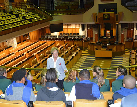 The Overstrand JTC listen with interest as Mayor Nicolette Botha-Guthrie explains that the Western Cape House of Parliament has sittings in the Chambers on matters concerning legislation of the province, is a forum for public debate, as well as being the body that oversees the Executive (government) and holds the government to account.